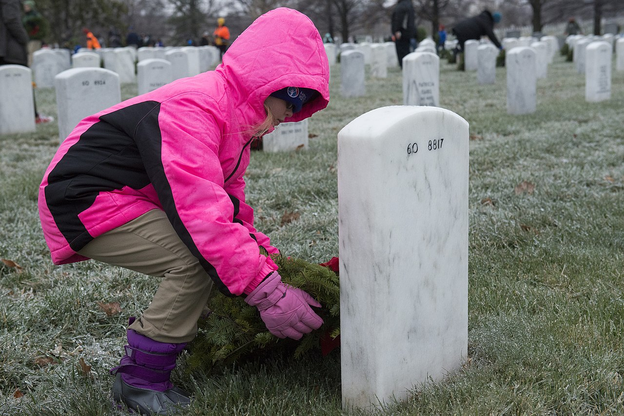 Child placing wreath on grave
